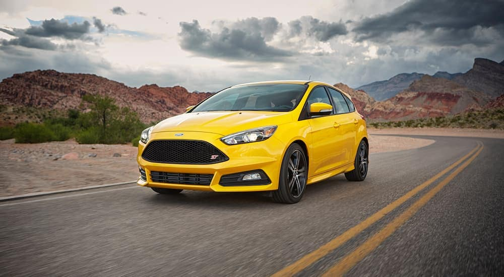 A yellow 2017 Ford Focus ST is driving on a desert road.