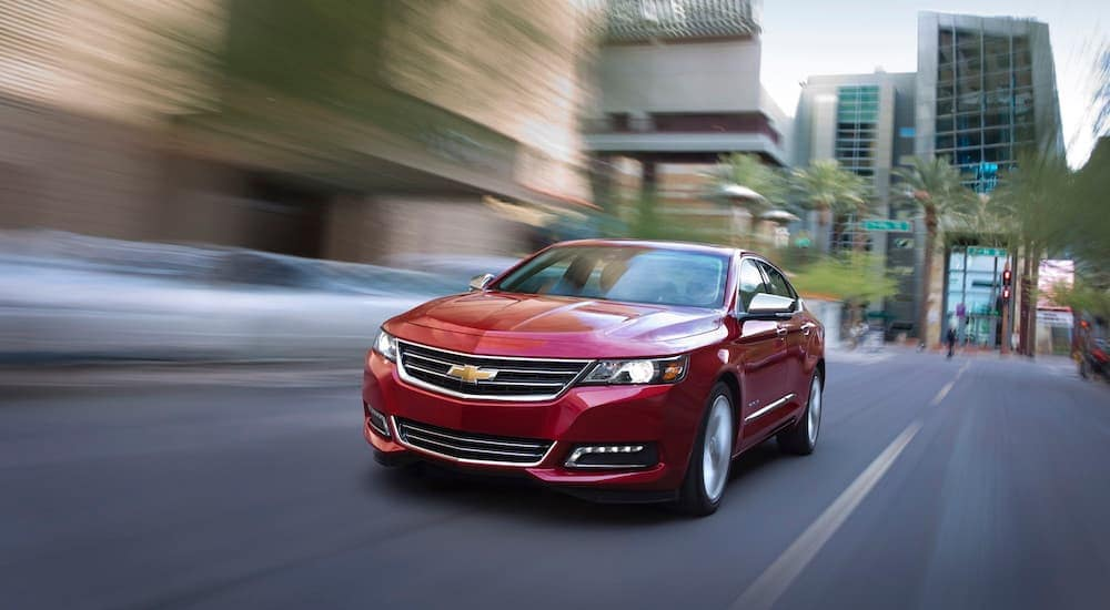 A red 2018 Chevy Impala from a used car dealer in Durham is driving on a city street.