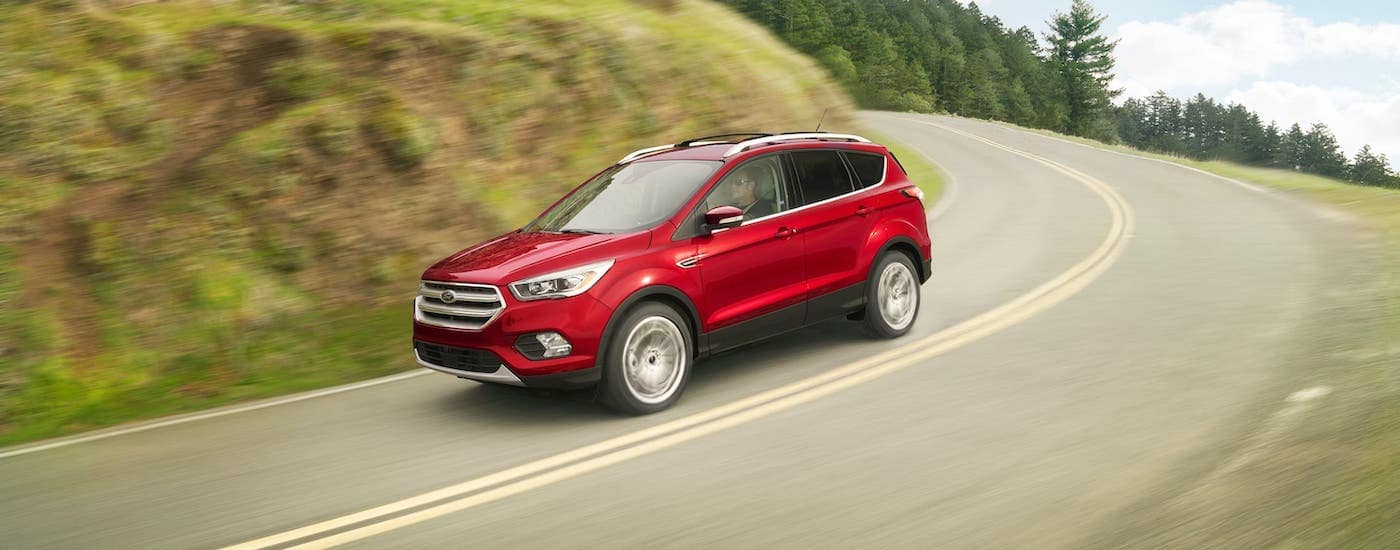 A red 2018 Ford Escape is driving around a corner on a hill.