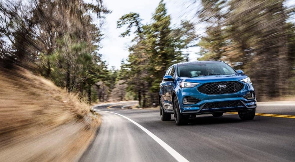 A blue 2019 Ford Edge is driving on a woodland road.