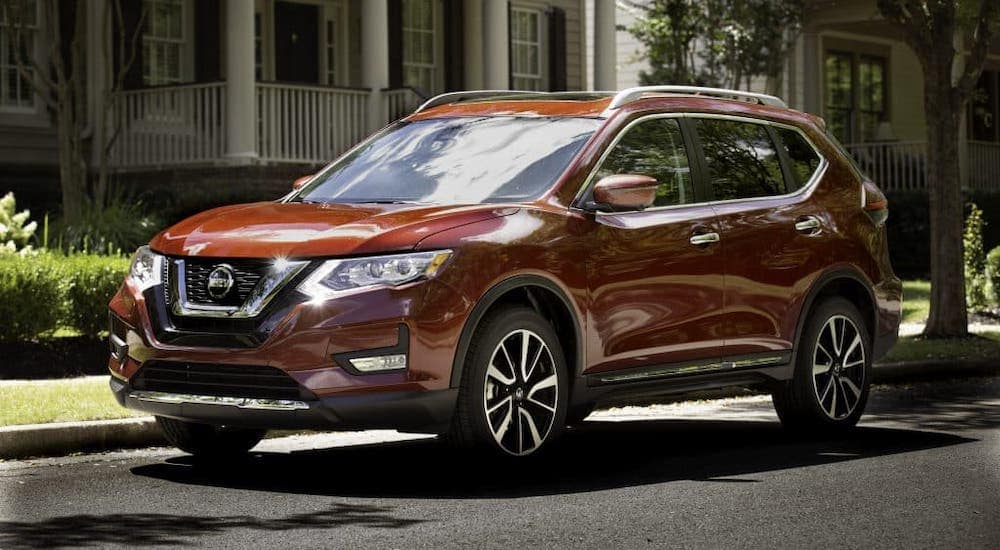 A popular used SUV for sale in Durham, NC, a dark red 2019 Nissan Rogue, is parked in front of a house.