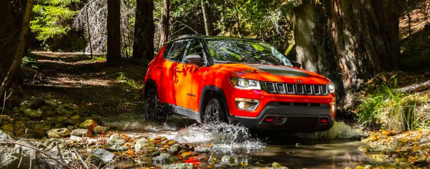 An orange 2020 Jeep Compass is driving through a river in the woods.
