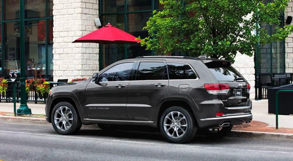 A popular used SUV for sale in Durham, NC, a gray 2020 Jeep Grand Cherokee, is parked in front of a whit brick building and tree.