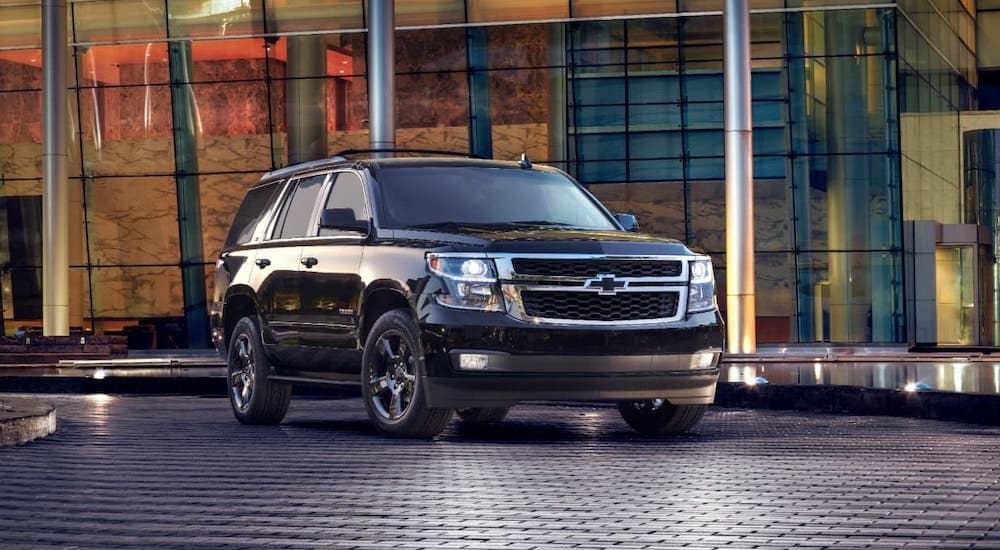 A black 2017 Chevy Tahoe is parked in front of a glass building after leaving a used car dealer in Durham.