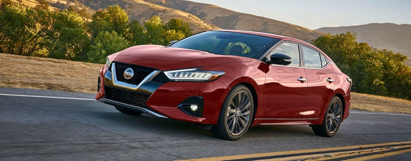 A red 2020 Nissan Maxima is driving on a highway in front of hills.