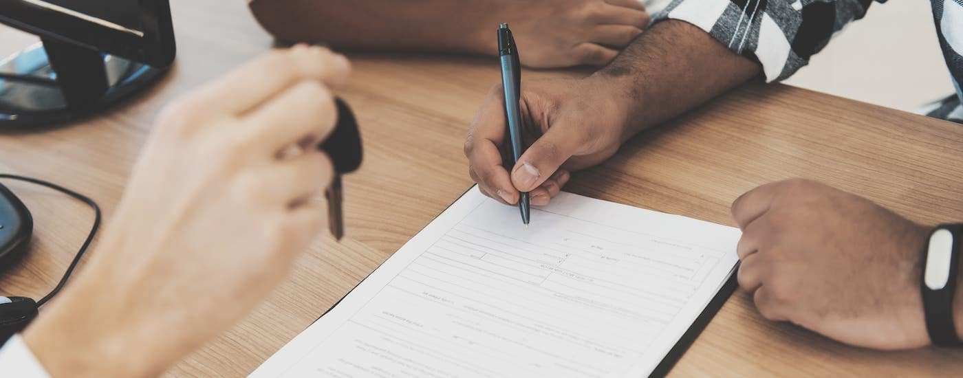 A closeup shows someone signing paperwork while a salesman hold a car key.
