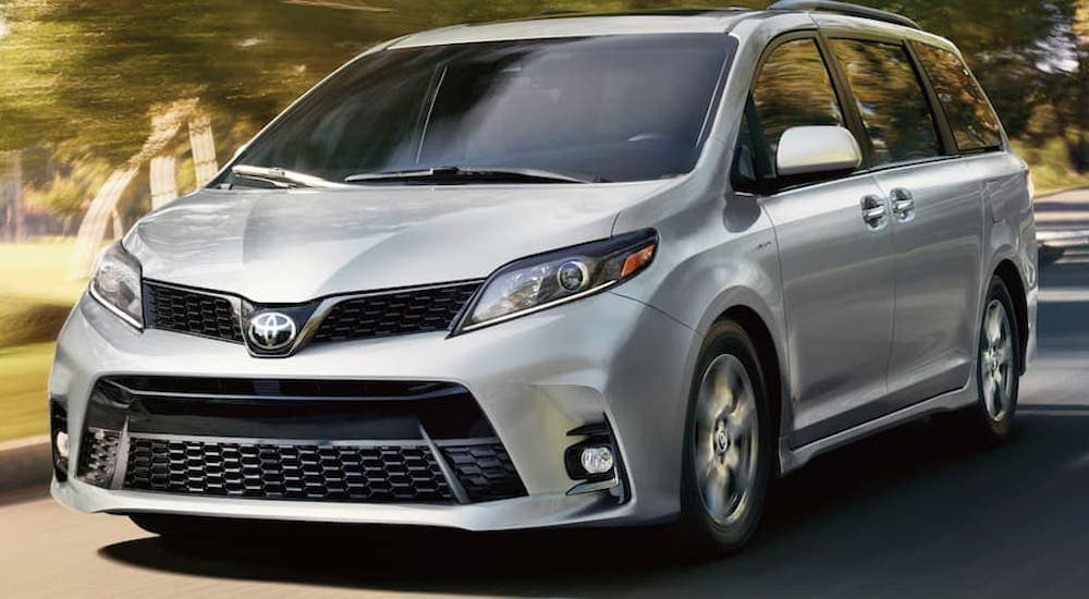 A silver 2020 Toyota Sienna is driving on a neighborhood street.