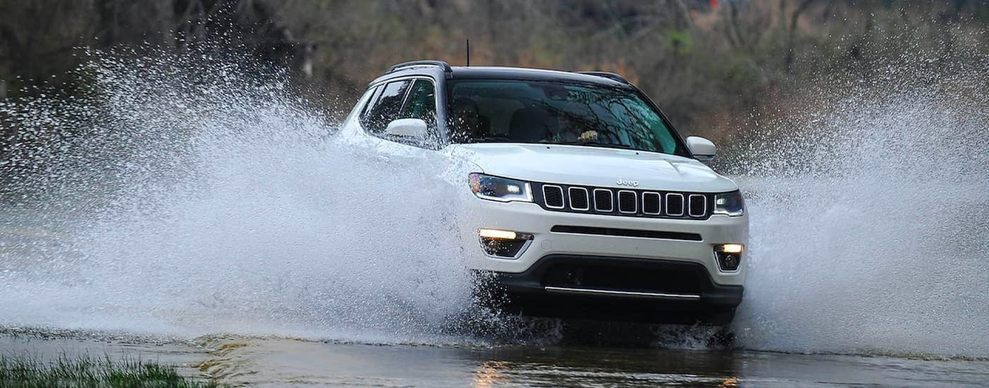 A white 2020 Jeep Compass is shown from the front splashing through a river.