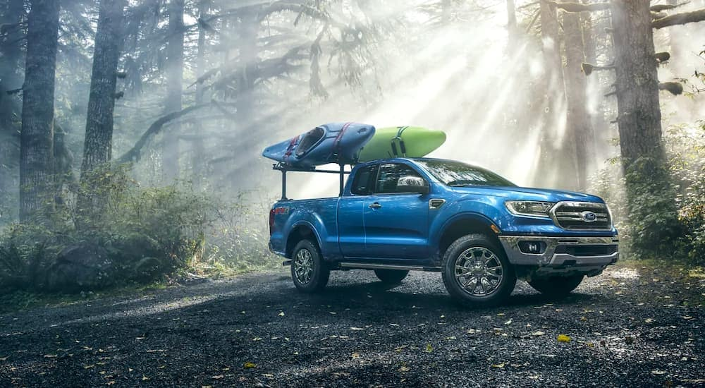 A popular used truck in Durham, NC, a blue 2020 Ford Ranger Lariat FX4, is shown parked in the woods with kayaks mounted over the bed.