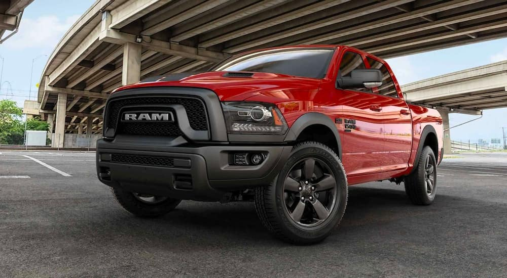 A red 2020 Ram 1500 Classic Warlock is shown parked under and overpass.