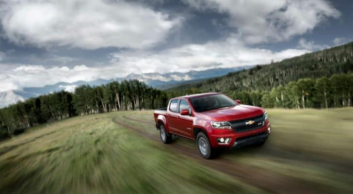 A popular used diesel truck in Durham, NC, a red 2015 Chevy Colorado Z71, is shown from high angle driving thorough the woods on a dirt path on a hill.