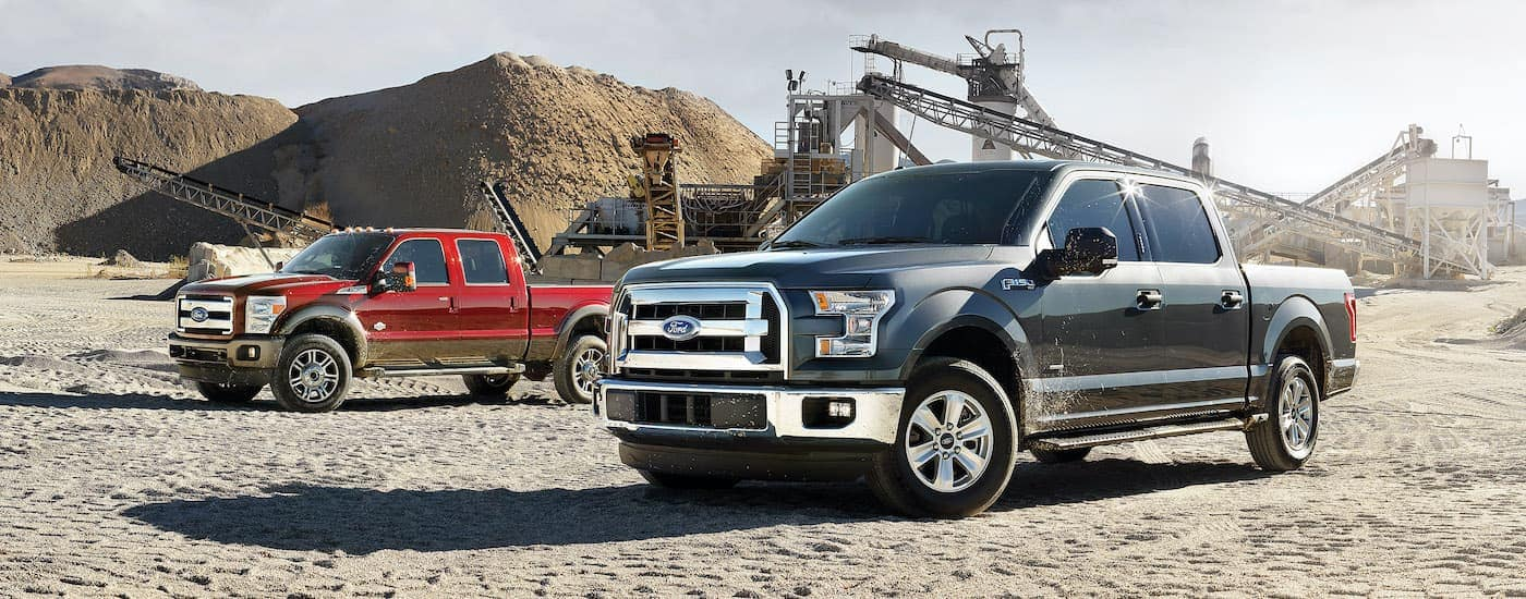 A red 2015 Ford F-150 and a grey 2015 F Series SuperDuty are shown from the side parked at a quarry.