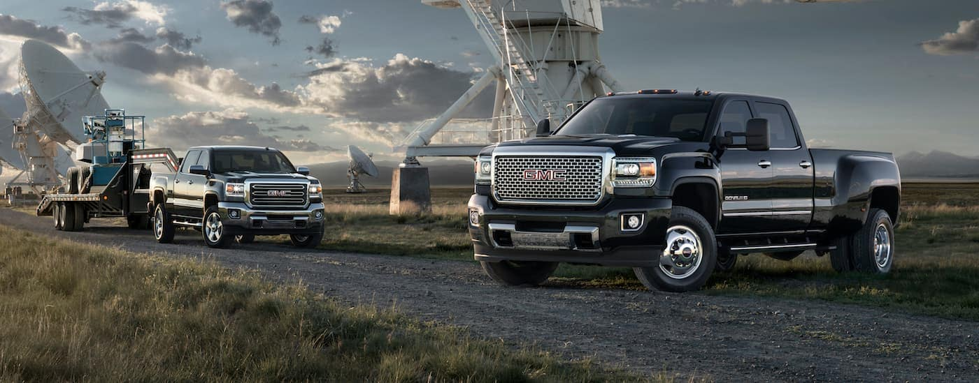 A black 2015 GMC 2500HD SLT and a black GMC 3500HD Denali are angled towards each other with satellite dishes in the background.