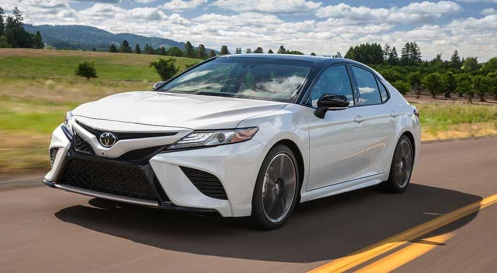 A white 2018 Toyota Camry is driving down a two lane road past a field after searching for used cars in Durham.
