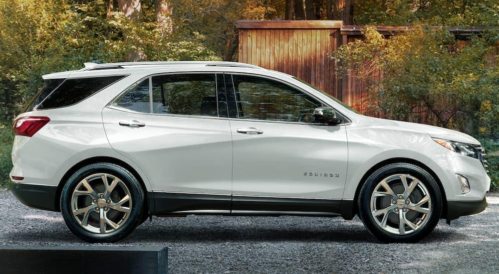 A white 2020 Chevy Equinox is shown from the side parked in a modern gravel driveway.