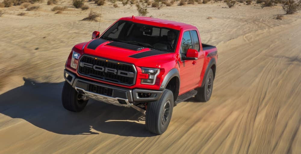 A red 2020 Ford F-150 is driving down a dirt road in the desert after looking for used cars in Durham.
