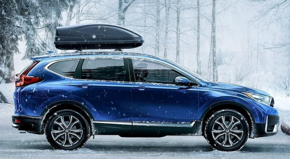 A blue 2020 Honda CRV AWD Touring is shown parked at a trail head in winter.