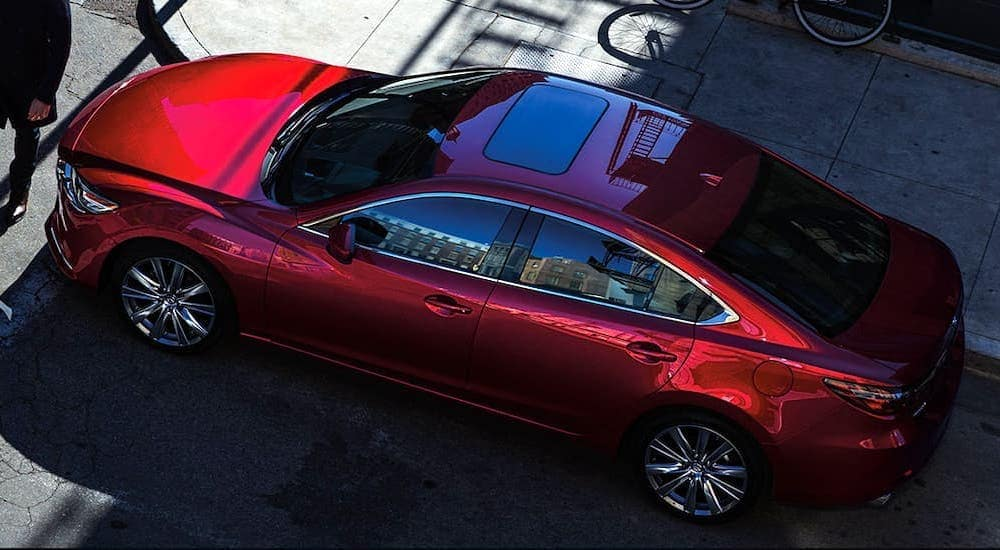 A red 2020 Mazda6 is shown stopped on a city corner.