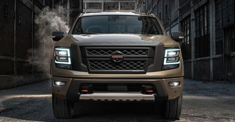 A tan 2020 Nissan Titan is shown from the front parked in an alleyway.