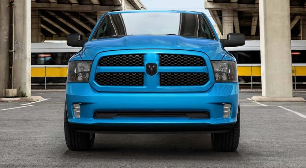 A blue 2020 Ram 1500 is shown from the front parked in a parking garage.