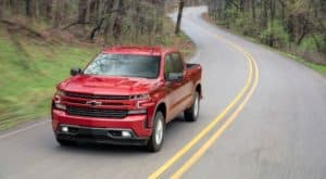 A red 2019 Chevy Silverado RST is shown from a high angle driving down a winding road.