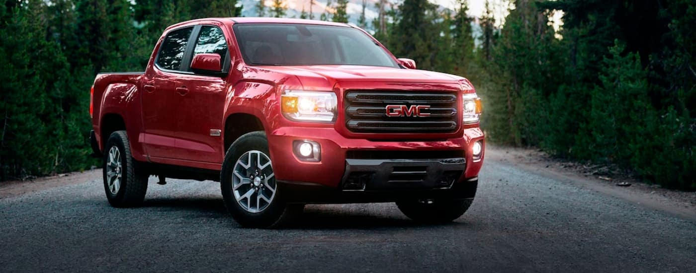 A red 2020 GMC Canyon, popular among GMC trucks, is parked on a road in front of pine trees.