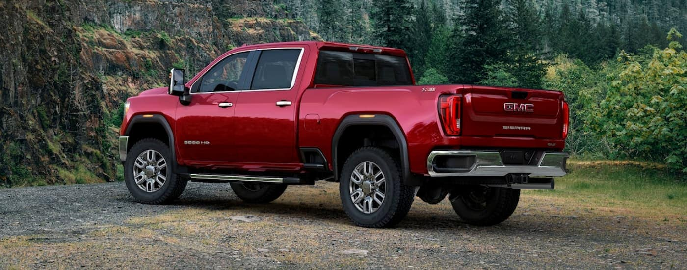 A red 2020 GMC Sierra 3500HD is parked off-road in front of trees.