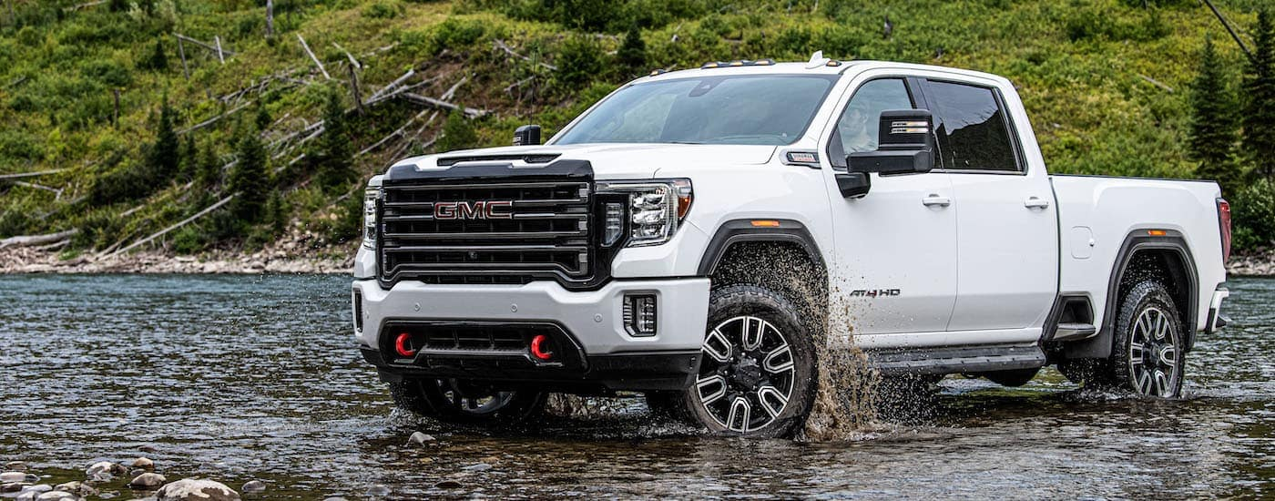 A white 2020 GMC Sierra HD AT4 is crossing a river.