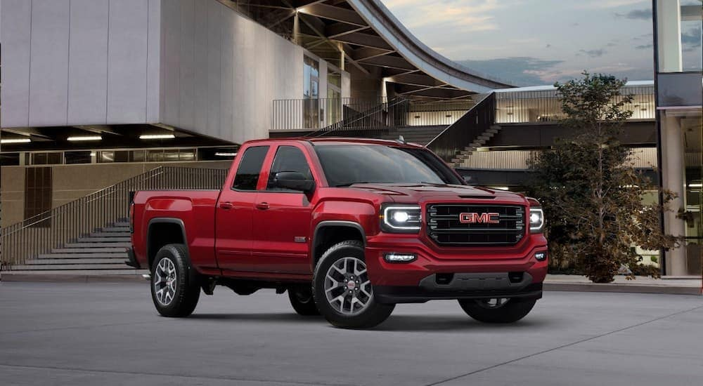 A red 2018 GMC Sierra is parked in front of a modern building with a large staircase.