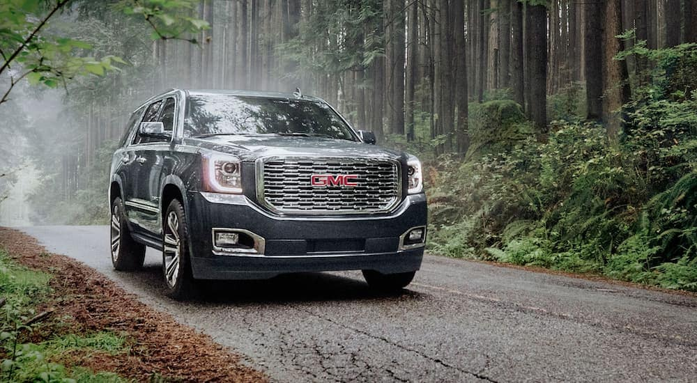 A grey 2020 GMC Yukon is driving on a forest road after leaving a GMC dealer near me in Indiana, PA.