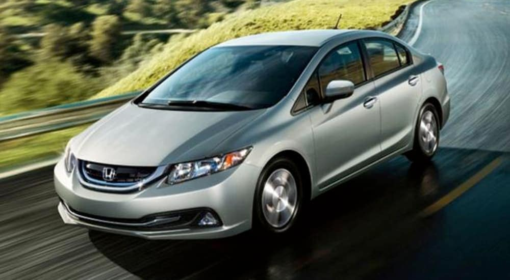 A silver 2014 Honda Civic, which is popular among used cars for sale, is driving on a winding highway.