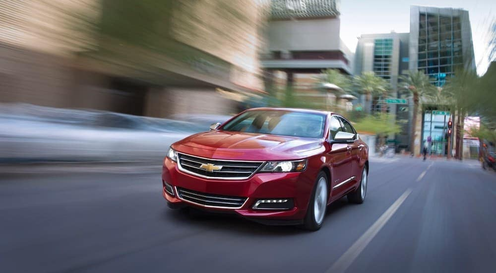 A red 2016 Chevy Impala is driving on a city street.