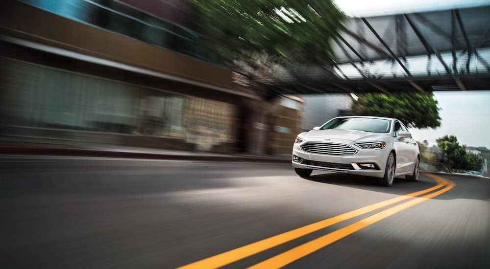 A white 2016 Ford Fusion is driving on a city street near Indiana, PA.
