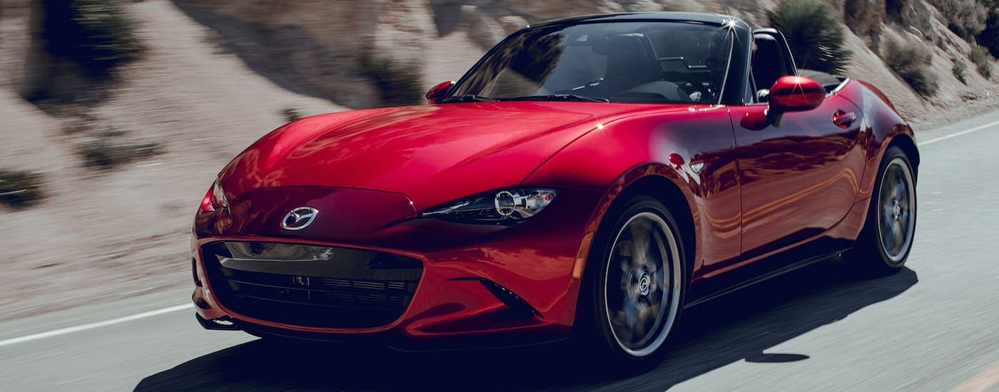A red 2019 Mazda MX-5 Miata is driving with the top down after leaving a Mazda dealer.