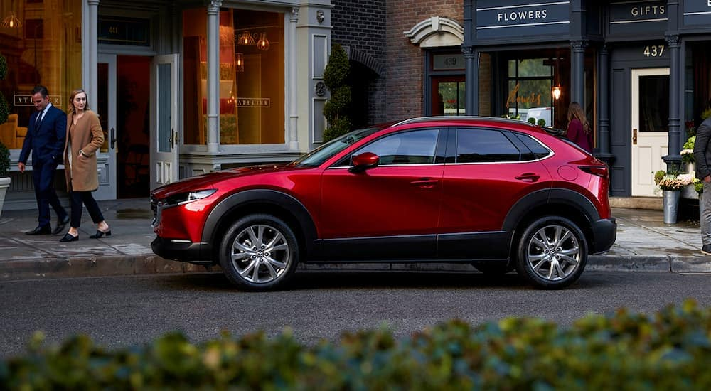A red 2020 Mazda CX-30 is parked on a city street after leaving a Mazda dealer.