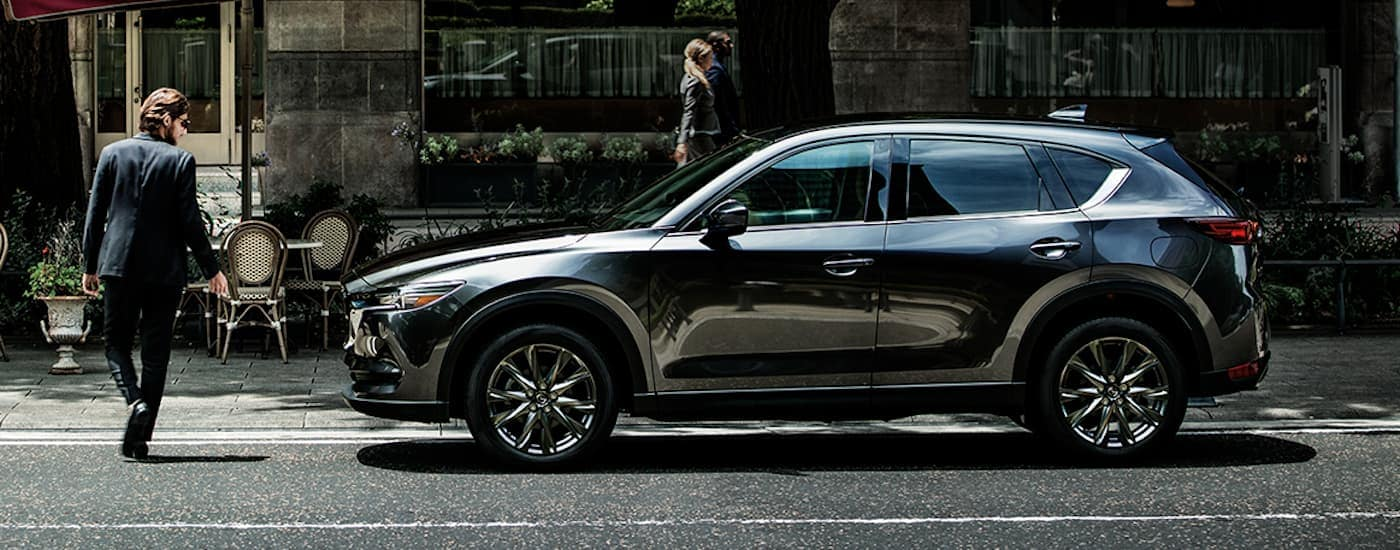 A dark grey 2020 Mazda CX-5 is parked on a city street while a man is looking at it.