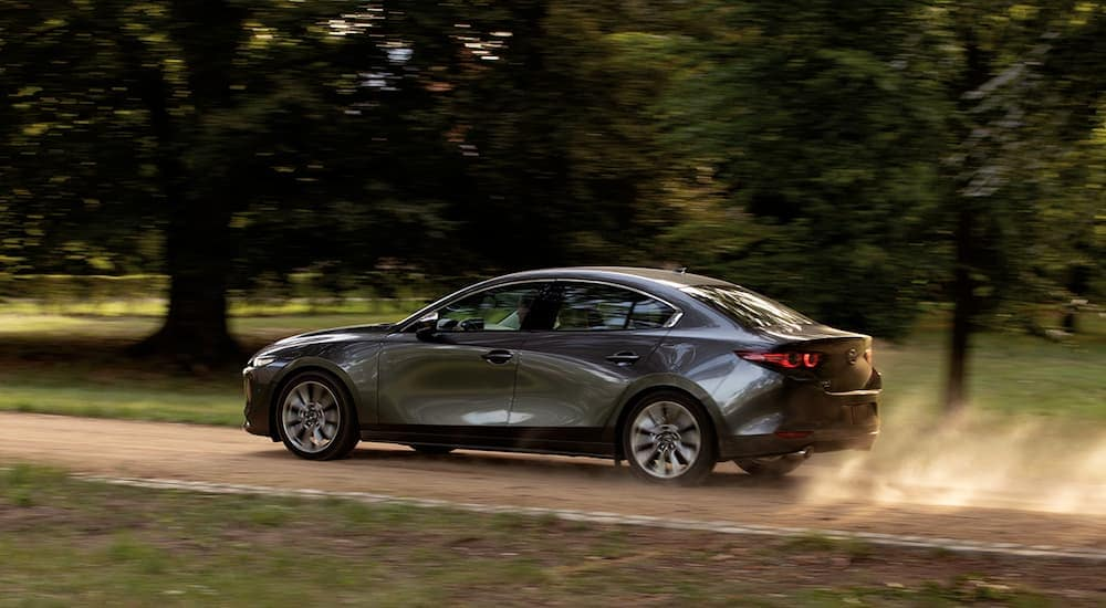 A grey 2020 Mazda3 is driving on a dirt road near Indiana, PA.