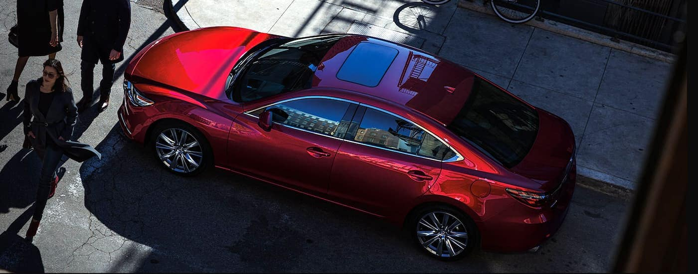 A red 2020 Mazda6 is shown from above on a busy street after leaving a Mazda dealer.