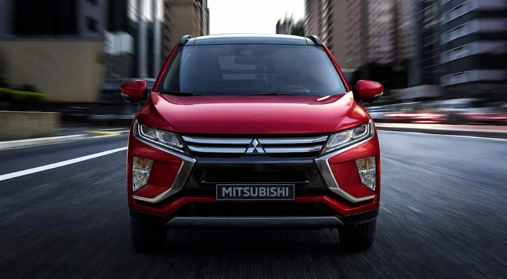 A red 2020 Mitsubishi Eclipse Cross is driving on a city street after leaving a Mitsubishi dealer.