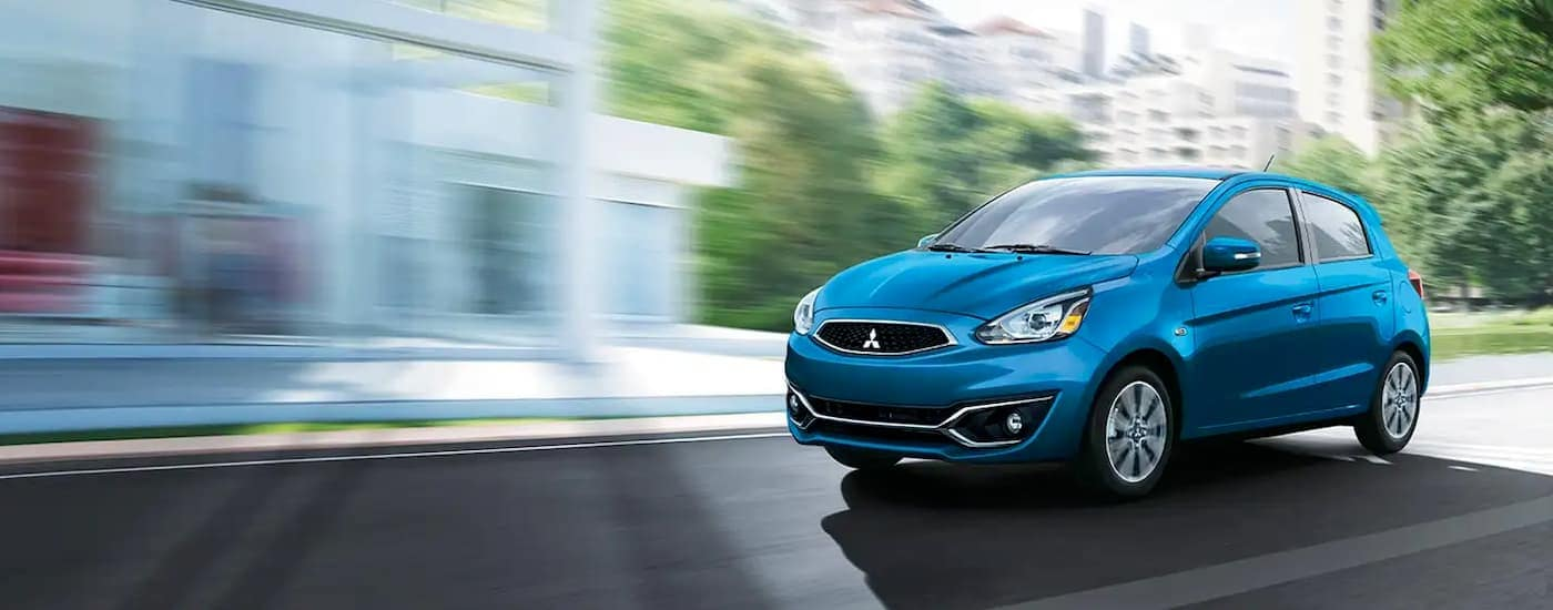 A blue 2020 Mitsubishi Mirage is driving in a city near Indiana, PA.