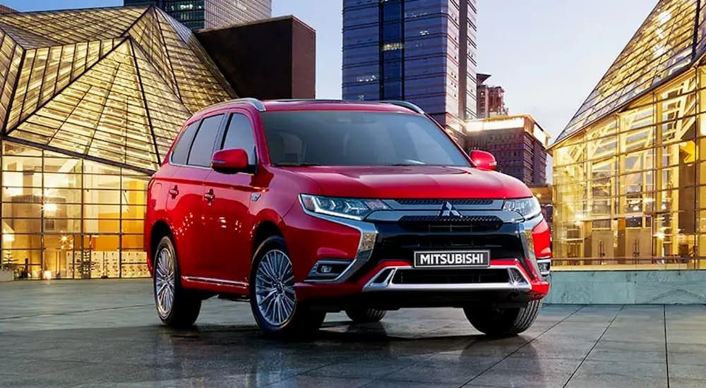 A red 2020 Mitsubishi Outlander PHEV is parked in front of city buildings.