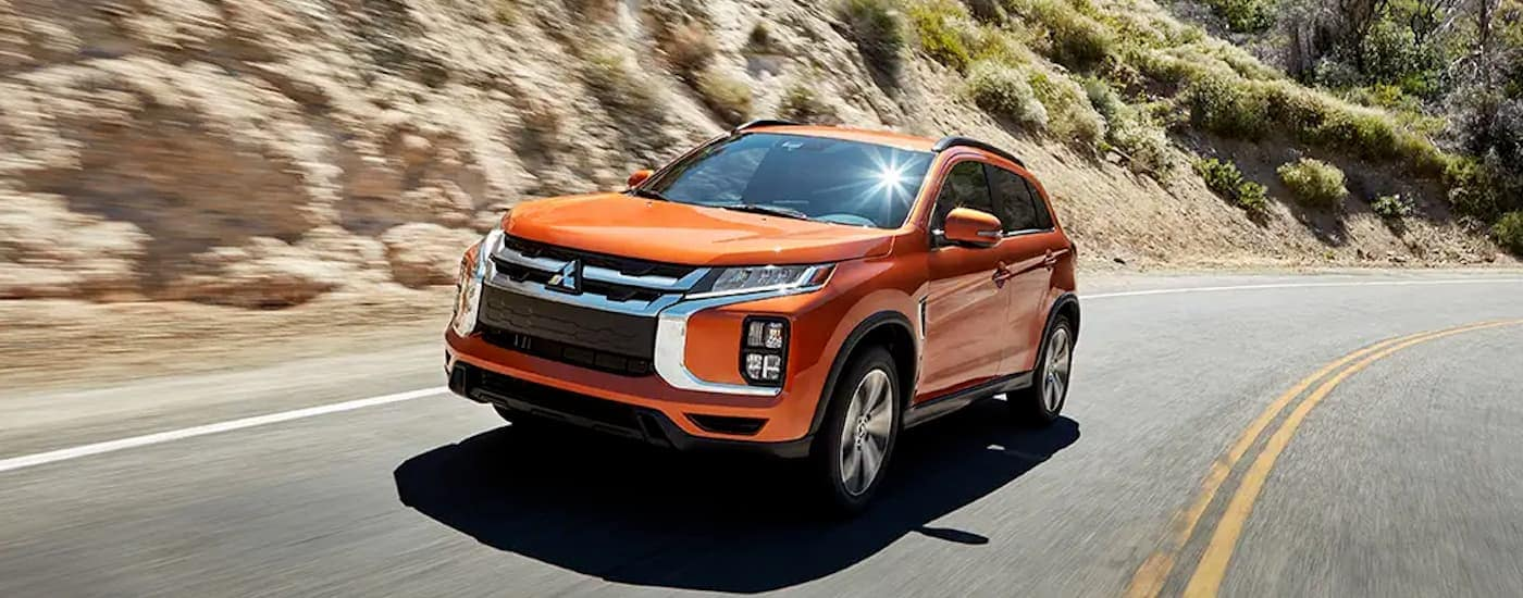 An orange 2020 Mitsubishi Outlander Sport is driving around a corner with a hill behind it.