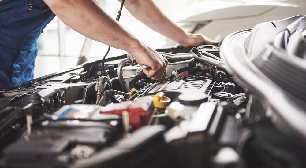 A mechanic is servicing a vehicle under the hood.