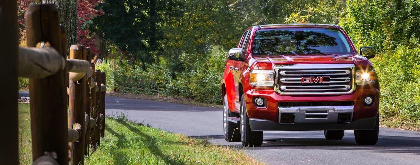 A red 2016 GMC Canyon is driving on a fence-lined road near Indiana, PA.