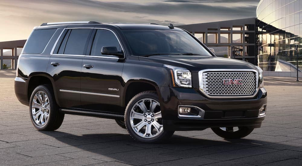 A black 2016 GMC Yukon Denali, which is popular among used cars for sale, is parked in front of a glass building.