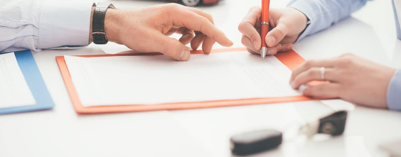 A close up of a salesman's hand pointing to where the buyer needs to sign on paperwork is shown.
