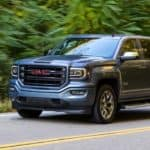 A grey 2016 GMC Sierra, popular among used cars near me, is driving on a tree-lined road.