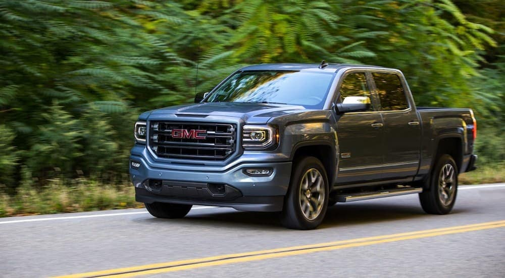 A grey 2016 GMC Sierra, which is popular among used cars near me, is driving on a tree-lined road.