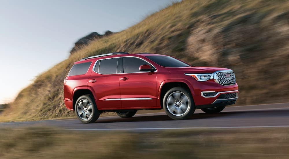 A red 2018 GMC Acadia Denali, which is popular among used cars near me, is driving up a hill.