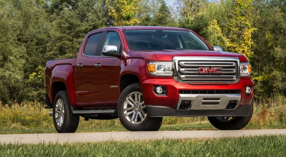 A red 2018 GMC Canyon is parked in front of trees.